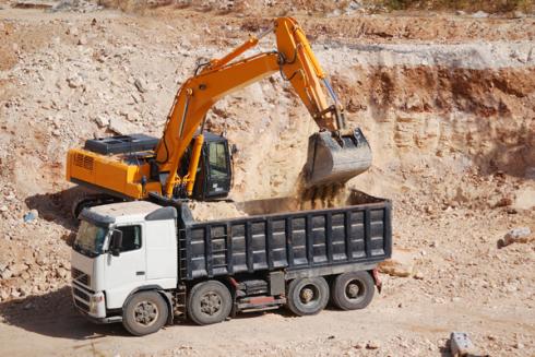 Escavatrice che carica un camion