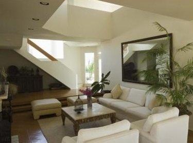 un salotto con divano,bianco, due poltrone e un tavolino