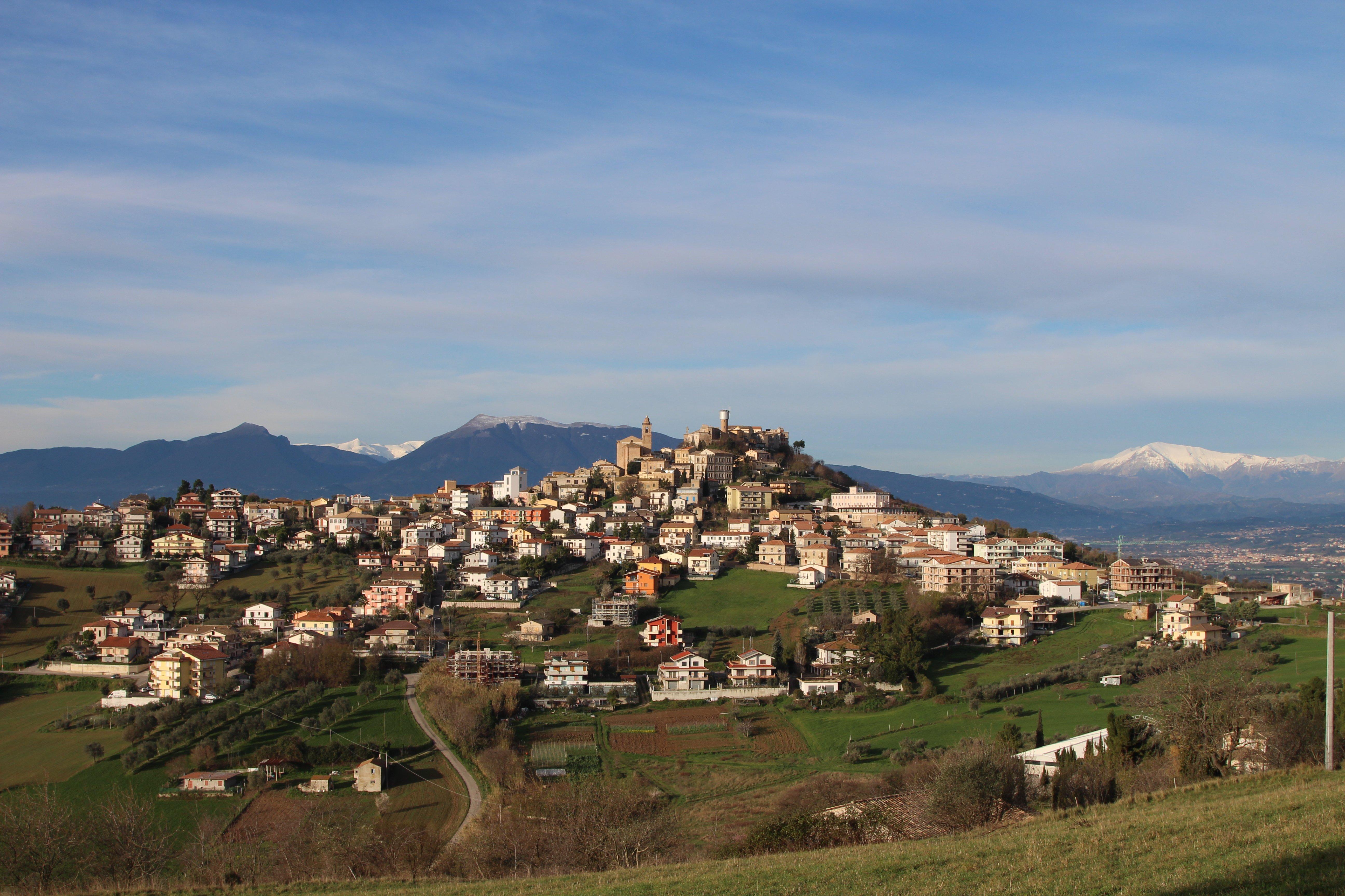 vallata con montagna innevata di sfondo e delle case