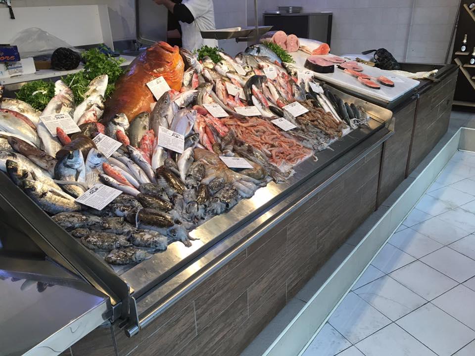 pesce fresco sul bancone della pescheria visto lateralmente