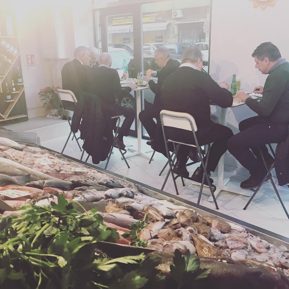 vista di alcune persone sedute e dietro vista del pesce esposto con delle foglie di rucola
