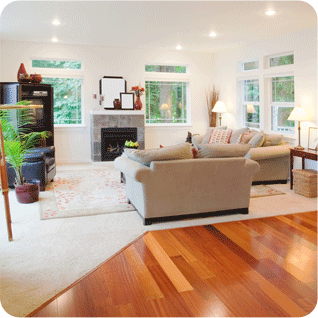 A living room with a mix of carpet and wood flooring