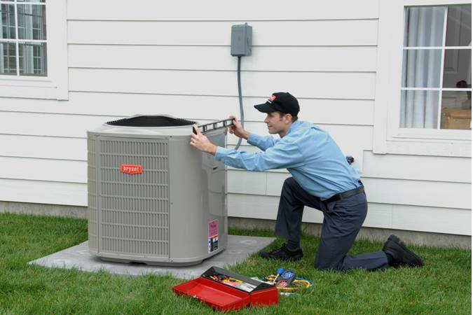 RMG Air Conditiioning and Heating Services working on an air conditioner outside a homne