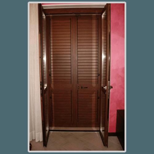 una porta finestra aperta con le tapparelle abbassate