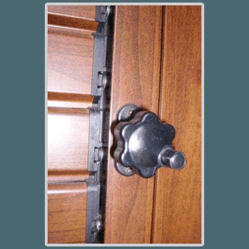 una  maniglia nera di una persiana in legno