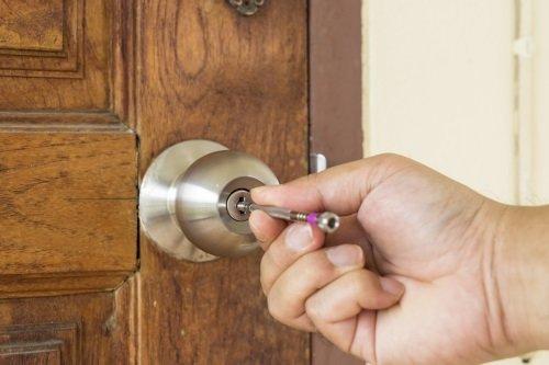 una mano con un oggetto infilato in una serratura