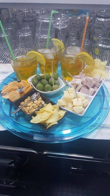 tre bicchieri di cocktail e accanto delle coppette di olive, patatine e altro