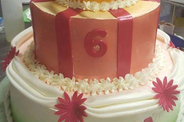 una torta a due piani con panna e glassa rosa con la scritta 6