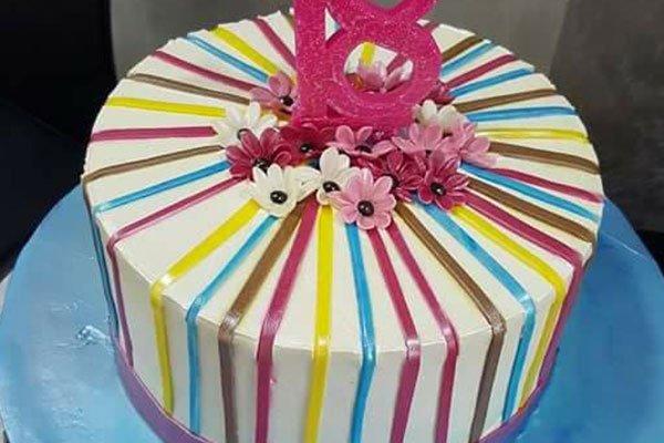 una torta alla panna con delle righe colorate dei fiori colorati e il numero 18 in fucsia
