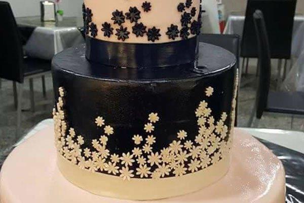 una torta a due piani di color nero con fiori bianchi