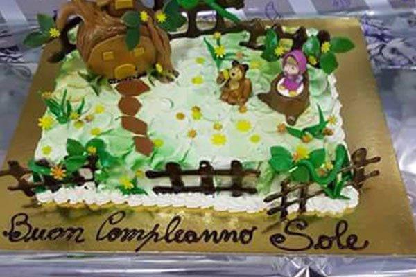 una torta di compleanno con dei pupazzi di un orso e una bambina