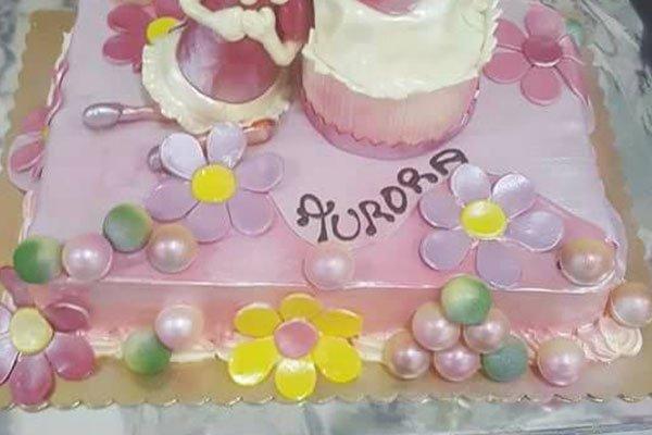 una torta color viola chiaro con dei fiori e la scritta Aurora