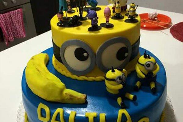 una torta gialla e blu in tema Minion