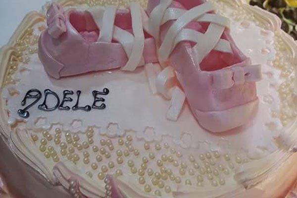 una torta con delle perle due scarpette di glassa fucsia e la scritta Adele