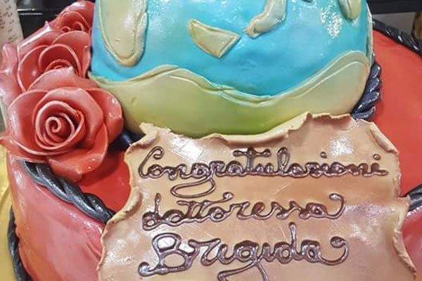 una torta particolare con scritto Congratulazioni Dottoressa Brigida