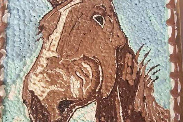 una torta azzurra con la testa di un cavallo marrone
