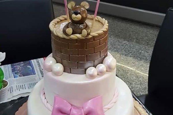 una torta di glassa bianca con un fiocco rosa e un orsetto marrone in cima
