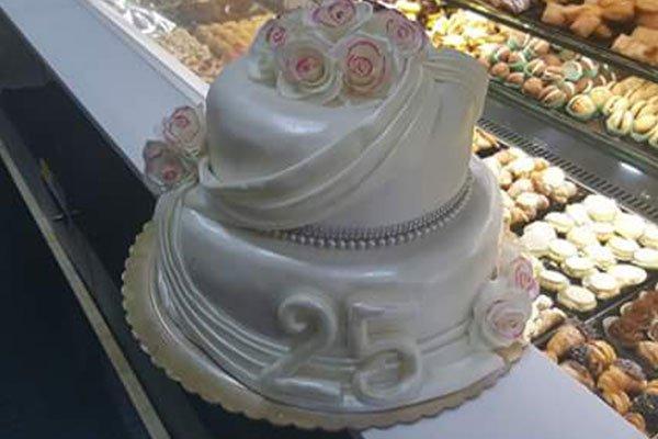 una torta a due piani con glassa bianca, delle rose e la scritta 25