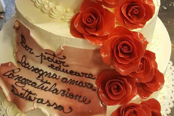 una torta a tre piani con delle rose rosse e la scritta per poter educare bisogna amare congratulazioni Dottoressa