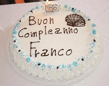 Un tavolo con una torta con scritto Buon compleanno Franco e una candela accesa