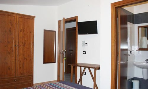 Una stanza con un letto, un armadio una tv e vista del bagno e un'altra porta aperta