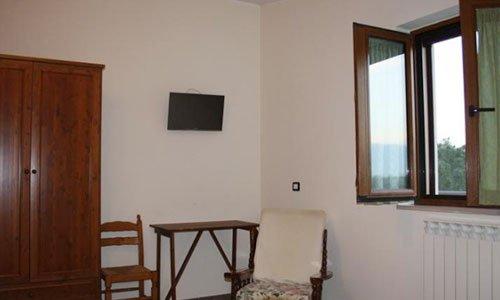 Una stanza con una poltrona in un angolo davanti a una finestra e sulla sinistra una scrivania e un armadio