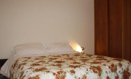 Una camera con un letto matrimoniale e un armadio sulla destra