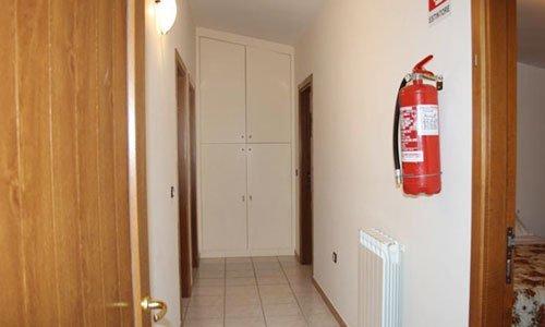 Un corridoio con un armadio bianco in fondo e un calorifero sulla destra
