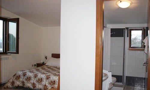 Vista di una camera con un letto matrimoniale e un bagno sulla destra con una box doccia,