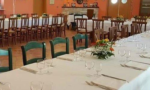 Una serie di tavoli apparecchiati con tovaglie bianche