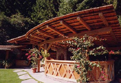 una tettoia in legno sotto una specie di ringhiera e dei fiori