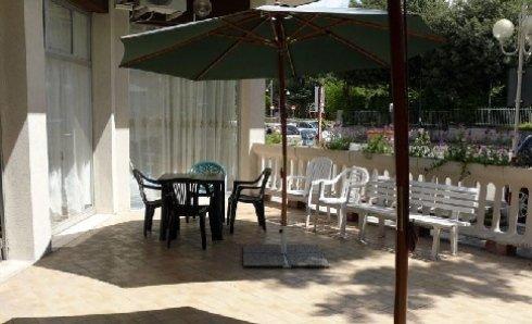 Sedie sotto un ombrellone nel giardino di Villa Sirente