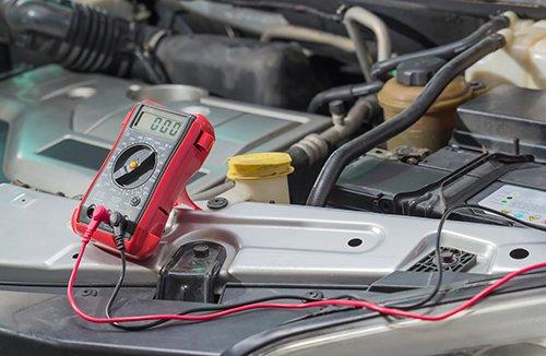 Meccanico controlla il livello della betteria dell'auto a Catania