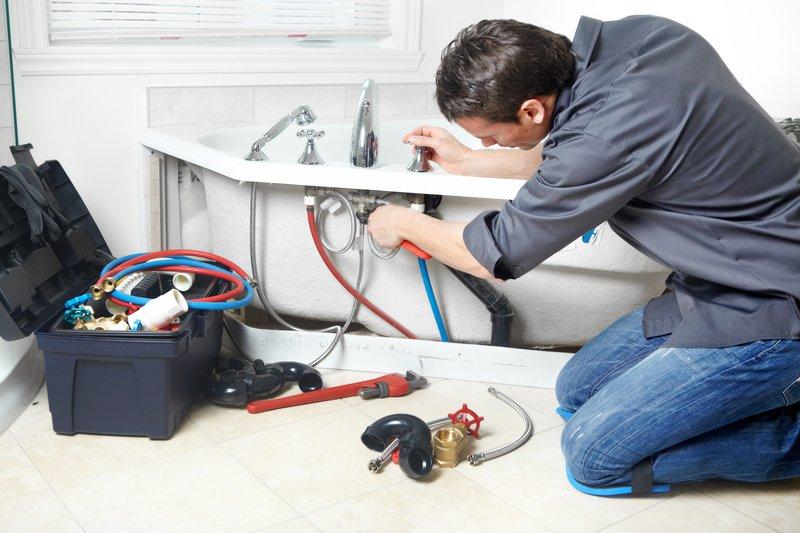 Plumber working underneath a sink