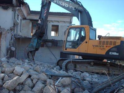 Escavatore vicino a un condominio in demolizione