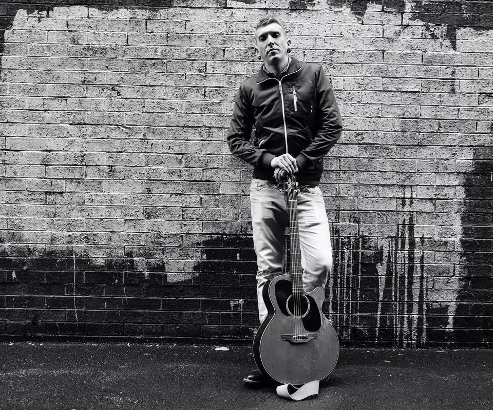Musician against brick wall