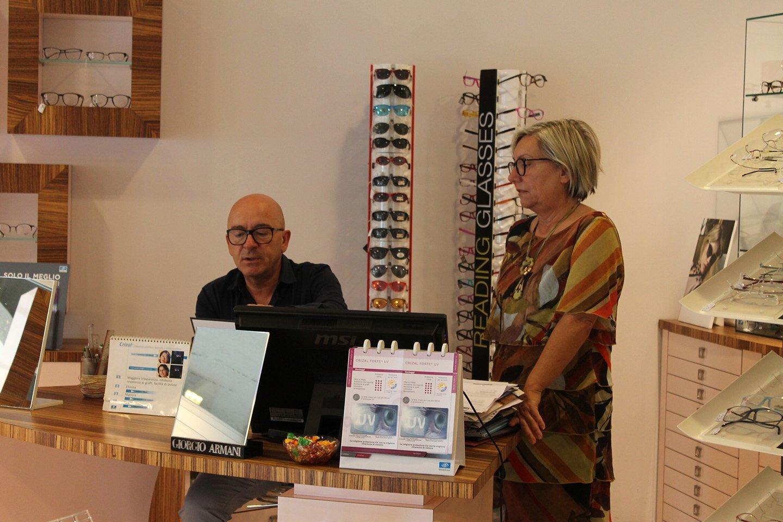 uomo seduto con bancone della optomeria mentre guarda un tablet e una donna è in piedi
