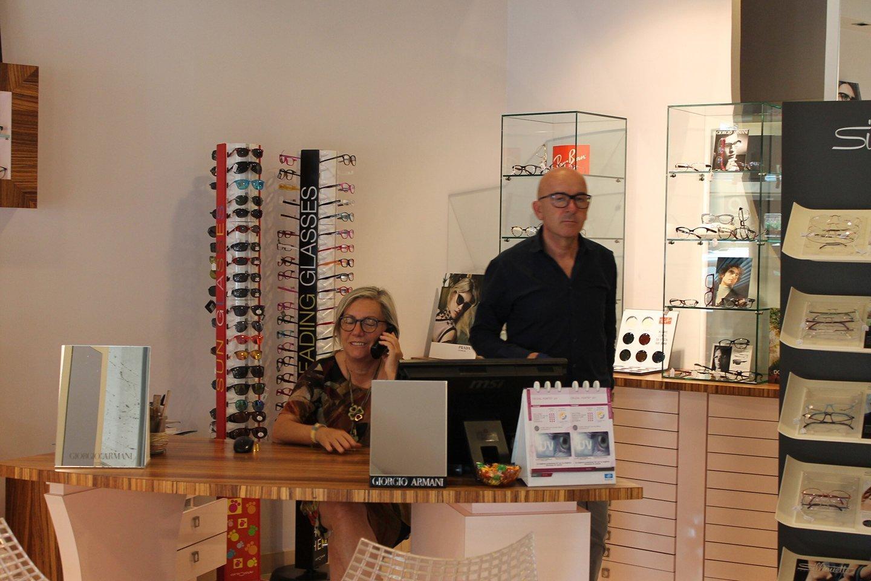 donna seduta con bancone della optomeria mentre parla al telefono e un uomo è in piedi