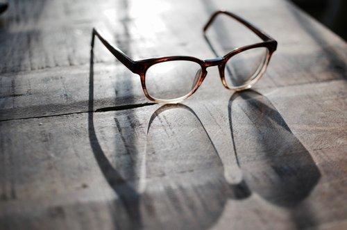occhiali da lettura su sfondo legno