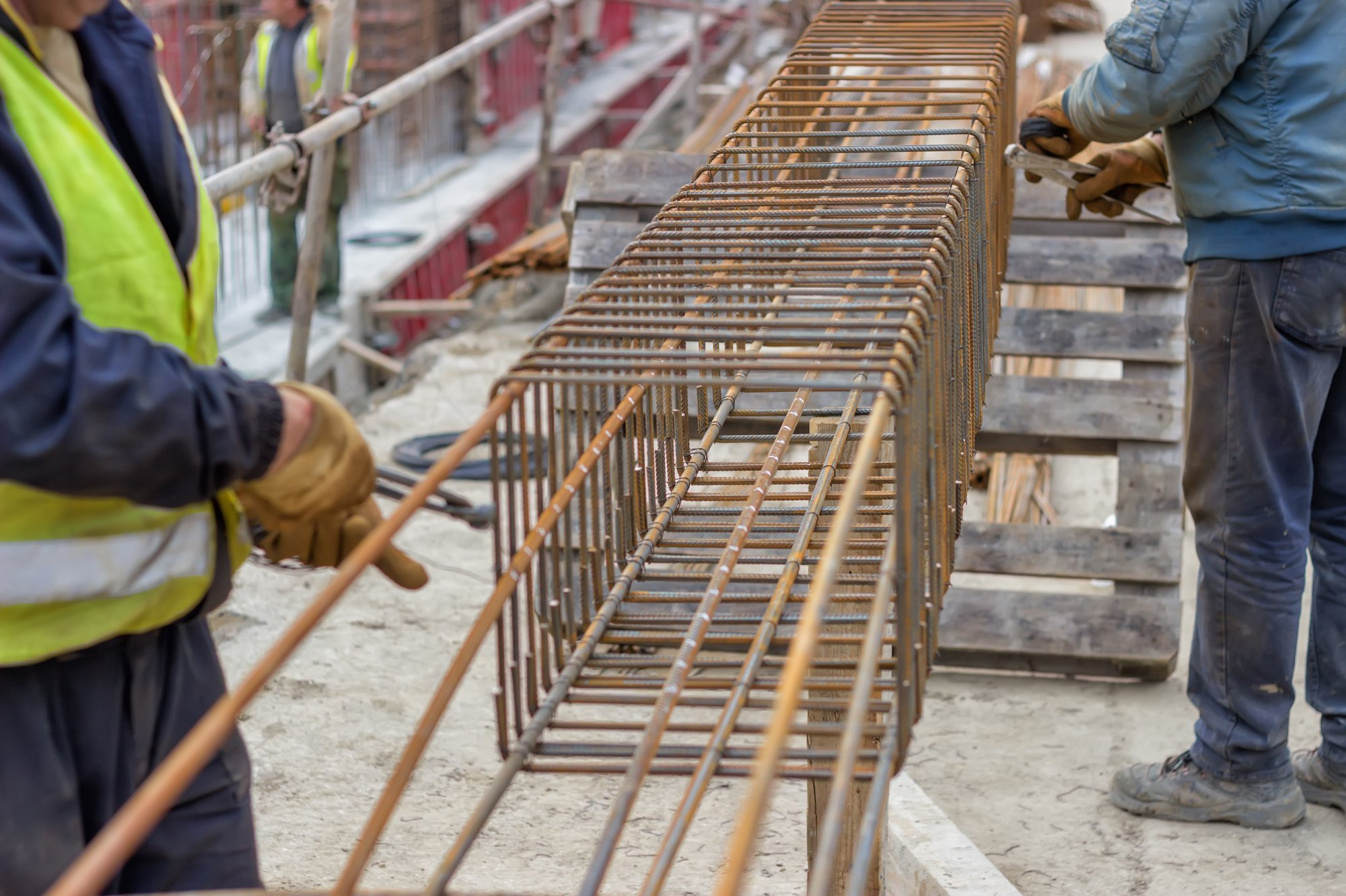 Steel reinforcement cage, beams are fabricated on the ground before being lifted into place. Selective focus on center portion of image.