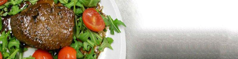 un piatto di carne con insalata e pomodori