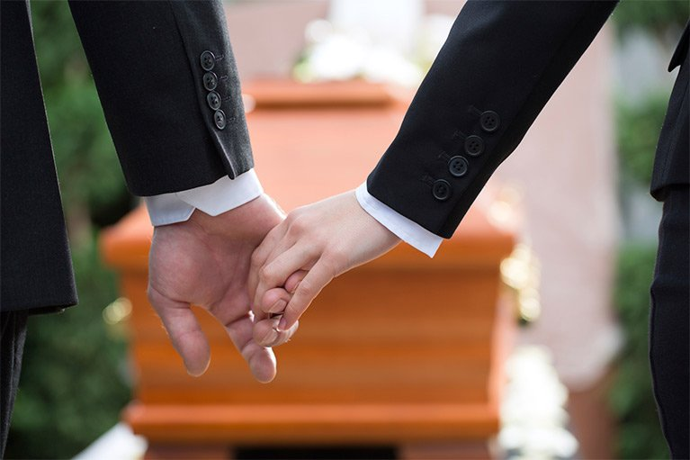 caring funerals hands together at funeral