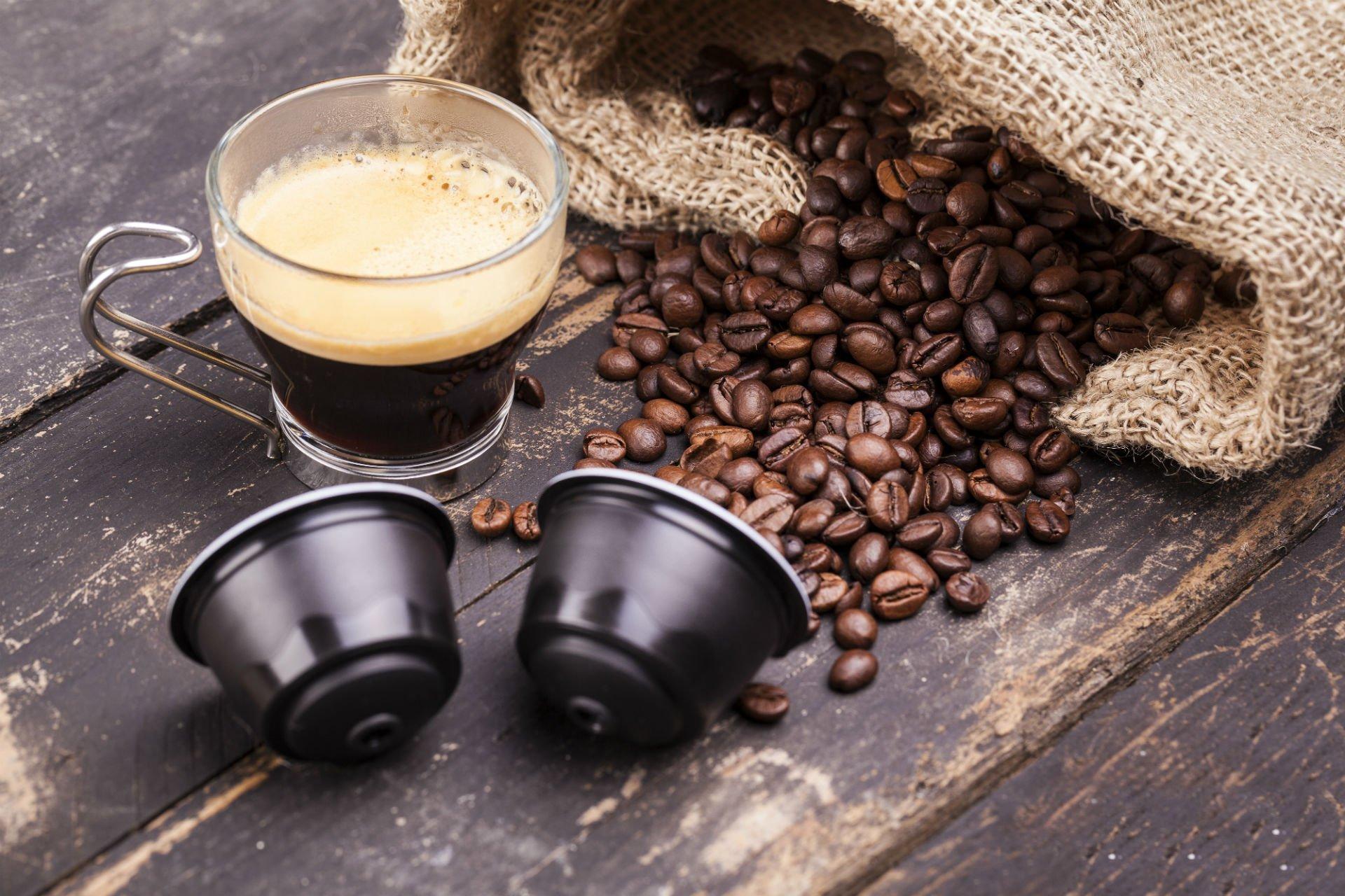 un sacco in juta con dei chicchi di caffè, due capsule e una tazza con del caffè'