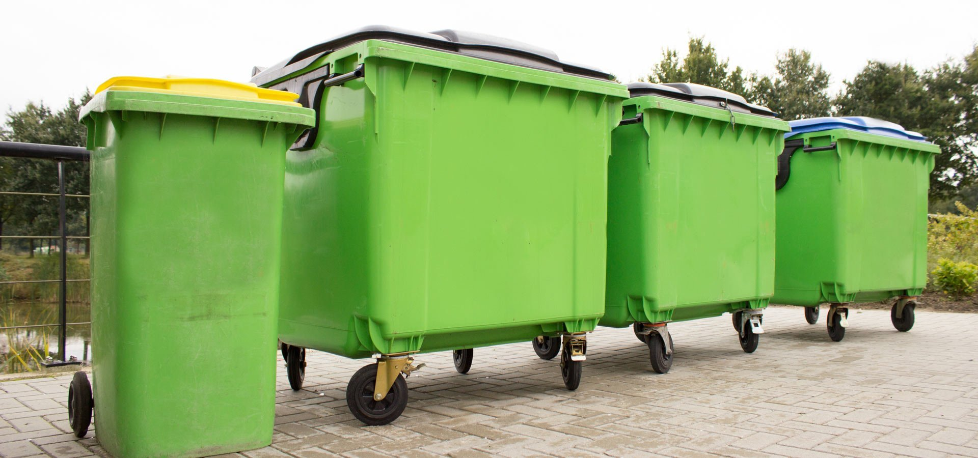 lightning bin hire four green garbage containers standing diagonally in a row