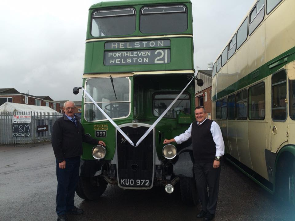 Men standing in front of a green double decker bus