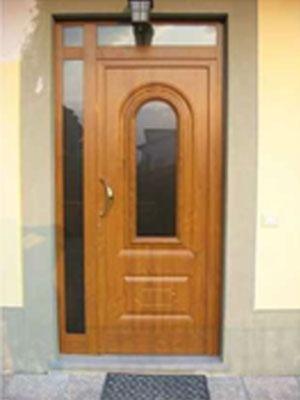 un portone in legno con una maniglia dorata e un vetro al centro