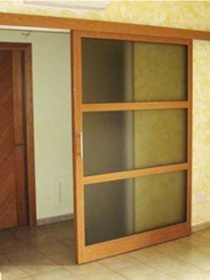 una porta scorrevole in vetro con finitura in legno
