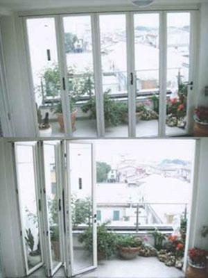 una porta finestra bianca e sul balcone dei vasi di fiori
