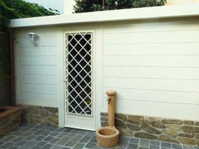 una porta bianca con una griglia all'esterno di una casa