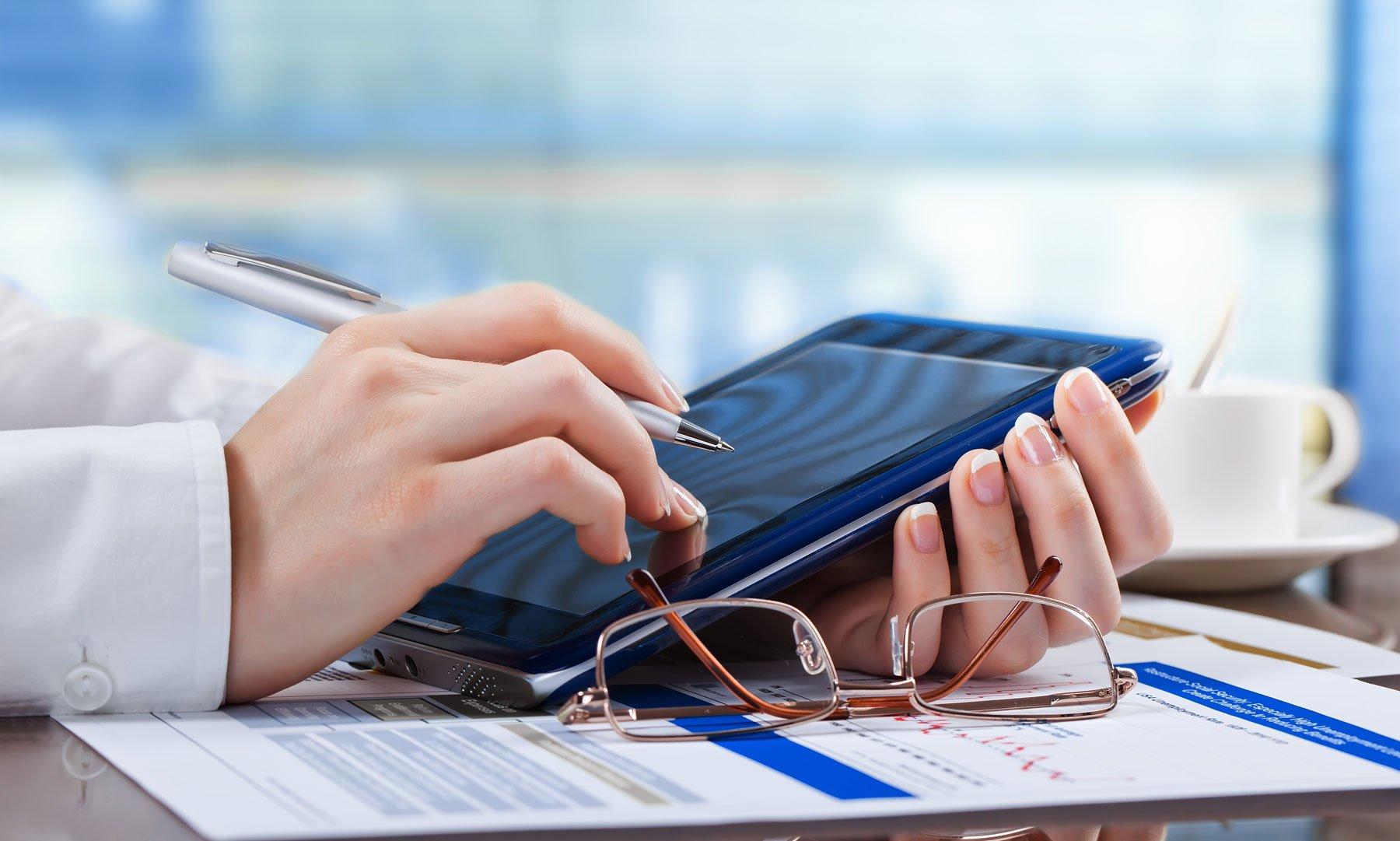 una mano con una penna in mano, un tablet  dei fogli su una scrivania e un paio di occhiali da vista